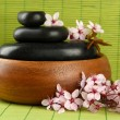 Spa stones and flowers on bamboo background — Foto Stock