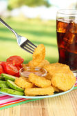 Fried chicken nuggets with vegetables,cola and sauce on table in park — Stock Photo