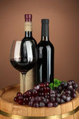 Composition of wine bottle, glass of red wine, grape on wooden barrel, on color background — Stock Photo