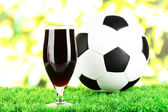 Glass of beer on lawn with ball — Stock Photo
