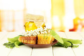 Jar of honey with flowers of lime, acacia on color wooden table on bright background — Stock Photo