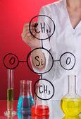 химик женщина, написание формул на стекле на красном фоне — Стоковое фото