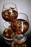 Brandy glasses with ice on grey background — Stock Photo