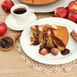 Stock Photo: Slice of tasty homemade pie with chocolate and apples and cup of coffee, on wooden table