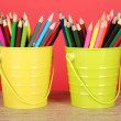 Colorful pencils in two pails on table on red background — Stock Photo #26794591