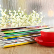 Many magazines with red cup on window background — Stock Photo #26795539