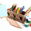 Different pencils in wooden crate, paints and easel, isolated on white — Stock Photo