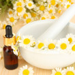 Essential oil and chamomile flowers in mortar on wooden table — Стоковая фотография