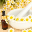 Essential oil and chamomile flowers in mortar on wooden table — Stock Photo