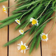Many spikelets and chamomile on wooden background — Foto de Stock