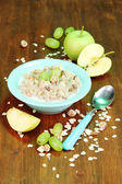 Useful oatmeal in bowl with fruit on wooden table close-up — Stock Photo