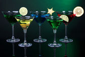 Alcoholic cocktails in martini glasses on dark green background — Stock Photo