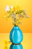 Beautiful bouquet of freesia in vase on orange background — Stock Photo