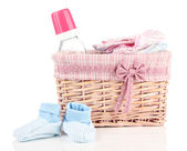 Beautiful basket of baby clothes isolated on white — Stock Photo