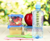 Tasty lunch in plastic containers, on wooden table on bright background — Stock Photo