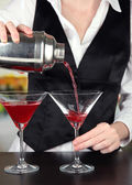 Barmen hand with shaker pouring cocktail into glasses, on bright background — Stock Photo