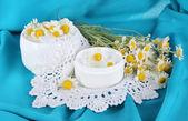Cream with chamomile on napkin on blue fabric background — Stock Photo