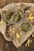 Medicinal Herbs in glass bowls on bagging close-up — Stock Photo