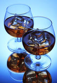 Brandy glasses with ice on blue background — Stock Photo