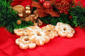 Christmas cookies and decorations on color fabric background — Stock Photo