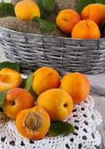 Apricots in basket on napkin on wooden table — Stock Photo