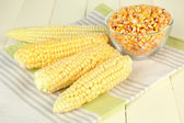 Fresh and dried corn on wooden background — Photo