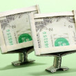 Dollars folded into computer monitors on green background — Stock Photo