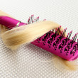 Comb brush with hair, on grey background — Stock Photo