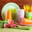 Multicolored plastic tableware on table with tulips on wooden background — Stock Photo #26826449