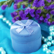 Flowers and engagement ring box on blue cloth — Stock Photo #26826933