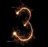 """Number """"three"""" sparklers on black background — Stock Photo"""