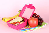 Lunch box with sandwich,fruit and stationery on pink background — 图库照片