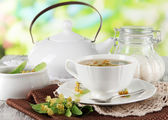Cup of tea with linden on napkins on wooden table on nature background — Stock Photo