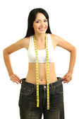 Beautiful young woman with big jeans and measuring tape isolated on white — Stock Photo