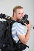 Portrait of handsome photographer with camera and tripod, on gray background — Stock Photo