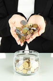 Saving, female hands putting coins into glass bottle, isolated on white — Stock Photo