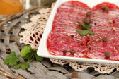Tasty salami on plate on wicker cradle isolated on white — Stock Photo