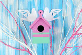 Decorative nesting box with paper birds and color branches, on color wooden background — Stock Photo