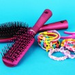 Scrunchies, hairbrush and hair - clip on blue background — Stock Photo #26903187