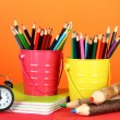 Colorful pencils in two pails with copybooks on table on orange background — Stock Photo