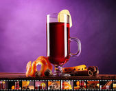Mulled wine in glass with photographic film of drinks on purple background — Stock Photo