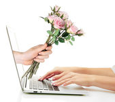 Male hand giving flowers to woman from laptop screen isolated on white — Stock Photo