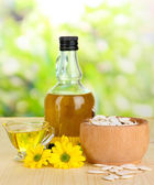 Useful pumpkin seed oil on wooden table on natural background — Stock Photo