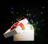 Gift box with red ribbon with sparkles on black background — Photo