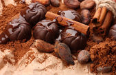Composition of chocolate sweets, cocoa and spices on brown background — Stock Photo