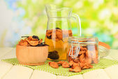Assorted dried fruits in bowl and compote of dried fruits on wooden table on natural background — Stock Photo
