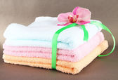 Towels tied with ribbon on gray background — Stock Photo