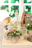 Chicken meat in glass bowl,herbs and spices on table on window background — Stock Photo