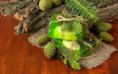 Hand-made soap and green pine cones on wooden table — Stock Photo