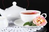 Kettle and cup of tea from tea rose on napkin black background — Stock Photo